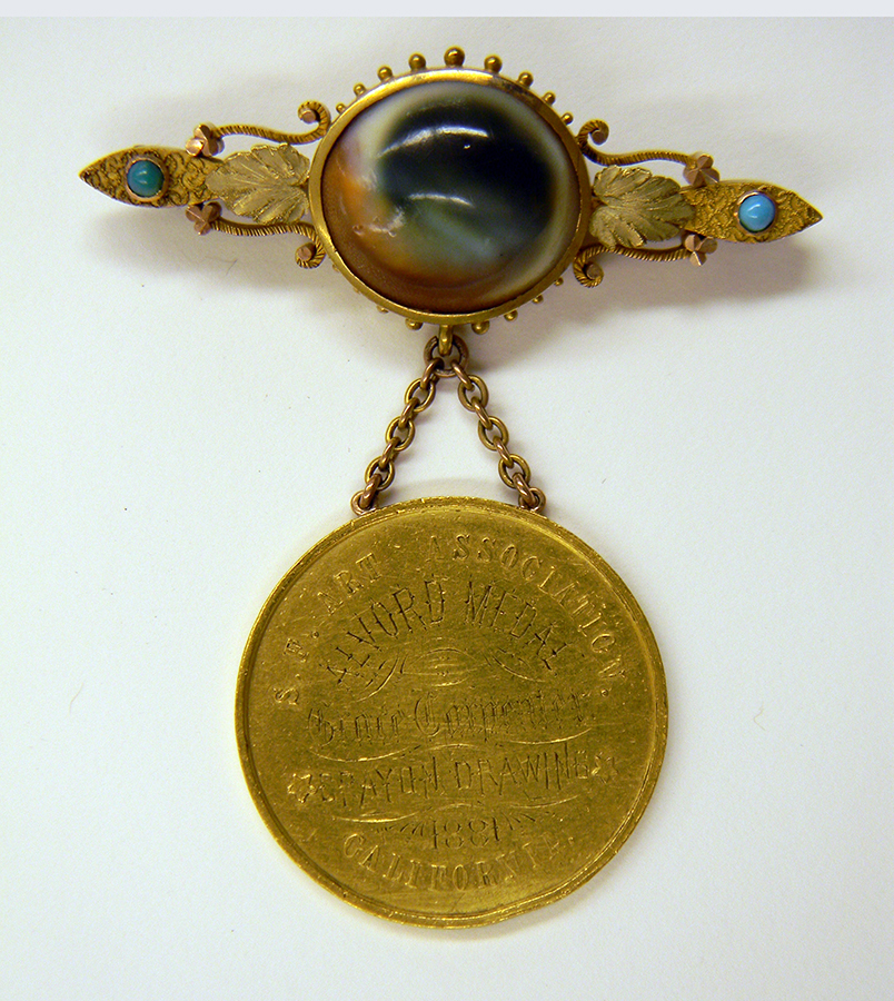 Courtesy of California Historical Society. Alvord Award, 1881. Maker unknown. Medallion 1 -1/2 inches, diameter; overall dimensions: 3 inches height x 2 -9/16 inches width. Gold, cat's eye shell, turquoise beads. California Historical Society, gift of Mr. and Mrs. Mark Carpenter.