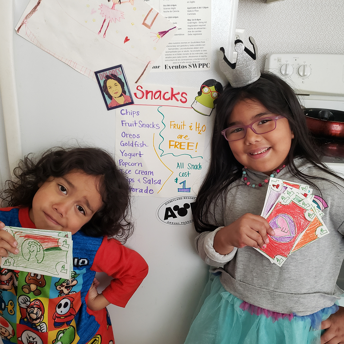 Gloria, photo of two children posing in front of a fridge for tell your story